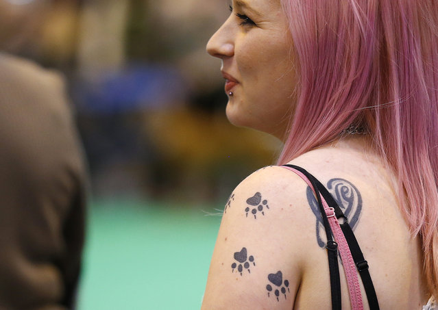 A woman sports dog paw print tattoos during the first day of the Crufts Dog Show in Birmingham, central England, March 5, 2015. (REUTERS/Darren Staples)