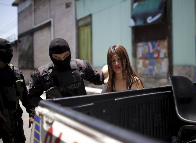 "A police officer detains a woman on suspicion of collaborating with the 18th street gang during a ""Safe House"" operation at the Concepcion neighbourhood in San Salvador, July 2, 2015. Salvadoran police make ""Safe House"" operations at dangerous neighbourhoods of the capital to prevent murders, according to local media. (Photo by Jose Cabezas/Reuters)"