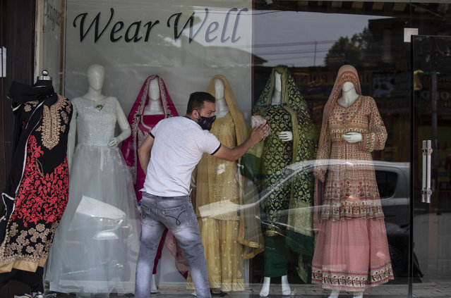 A Kashmiri shopkeeper cleans the display of his shop that was opened following a partial relaxation in the lockdown imposed to curb the spread of coronavirus in Srinagar, Indian controlled Kashmir, Monday, May 31, 2021. (Photo by Mukhtar Khan/AP Photo)