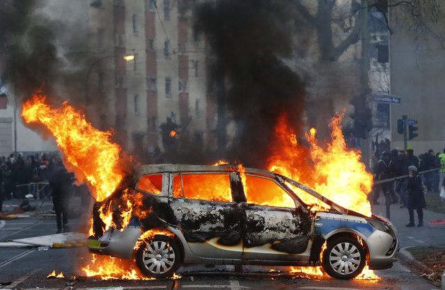 "A police car burns after clashes between demonstrators and police Wednesday, March 18, 2015 in Frankfurt, Germany. The ""Blockupy"" alliance said activists plan to try to blockade the new headquarters of the ECB to protest against government austerity and capitalism. (Photo by Michael Probst/AP Photo)"