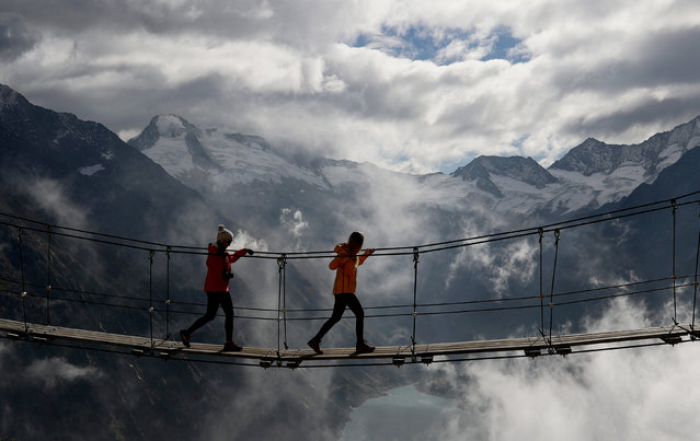 Women walk on a swing bridge beyond Schlegeis reservoir as fog rises on a sunny autumn day near the alpine village of Ginzling, Austria October 21, 2018. (Photo by Lisi Niesner/Reuters)