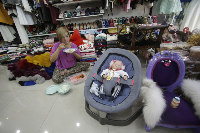 "In this Friday, January 29, 2016 photo, an employee of a clothing store eats lunch next to a ""child angel"" doll in Bangkok, Thailand. (Photo by Sakchai Lalit/AP Photo)"