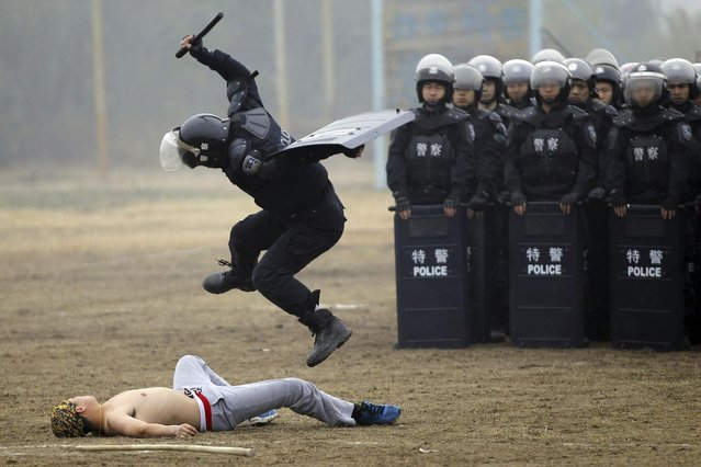 A policeman (2nd L) of the Special Weapons and Tactics (SWAT) controls a mock rioter during a SWAT police performance drill at a training base in Xi'an, on November 3, 2013. (Photo by Reuters/Stringer)