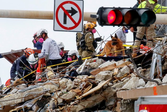 Emergency workers conduct search and rescue efforts at the site of a partially collapsed residential building in Surfside, near Miami Beach, Florida, U.S. June 29, 2021. (Photo by Joe Skipper/Reuters)