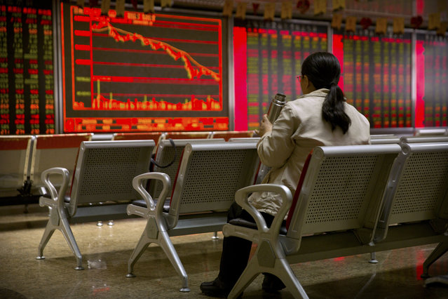 A Chinese investor monitors stock prices at a brokerage house in Beijing, Thursday, November 29, 2018. Asian stocks followed Wall Street higher on Thursday after U.S. Federal Reserve Chairman Jerome Powell suggested the pace of interest rate increases might slow. (Photo by Mark Schiefelbein/AP Photo)