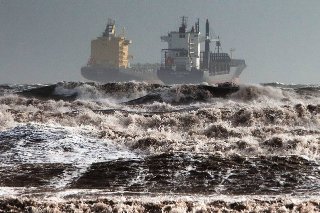 Two tankers are battered by gale winds while at the roadstead in the rough waters of the Gulf of Cagliari, Sardinia, Monday, November 18, 2013. A violent rainstorm that flooded entire parts of the Mediterranean island of Sardinia has led to the deaths of at least nine people. Bridges were felled by swollen rivers and water levels reached 3 metres (yards) in some places. (Photo by Max Solinas/AP Photo)