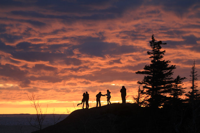 Three couples enjoy the spring equinox sunset over Turnagain Arm from Beluga Point on Saturday, March 21, 2015, in Anchorage, Alaska. (Photo by Dan Joling/AP Photo)