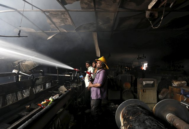 A firefighter tries to extinguish a fire that broke out in a textile mill in the western Indian city of Ahmedabad March 25, 2015. No causalities were reported and the cause of the fire is still unknown, a fire official said on Wednesday. (Photo by Amit Dave/Reuters)