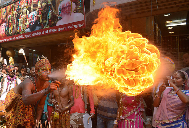 Indian dancers perform a fire breathing act during a procession to mark the 661st anniversary of the birth of Hindu guru Bawa Lal Dayal Maharaj in Amritsar on February 9, 2016. Bawa Lal Dayal Maharaj, a popular leader of his time, is especially revered by devotees of a temple in the town of Dhyanpur, some 45 kms north of Amritsar. (Photo by Narinder Nanu/AFP Photo)