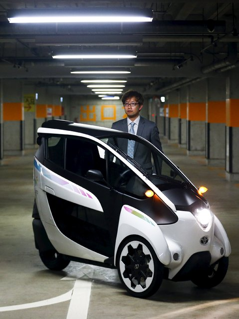 Toyota's i-Road chief engineer Akihiro Yanaka poses behind one of the electric vehicles that is to be used in a planned car sharing scheme in Tokyo April 9, 2015. (Photo by Thomas Peter/Reuters)