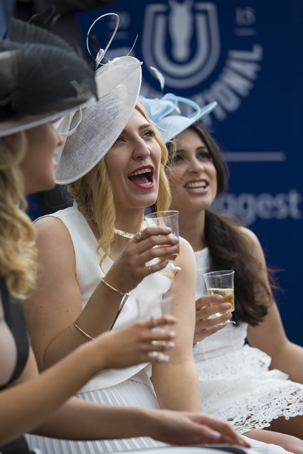 Spectators take refreshments during Aintree race meeting's Ladies Day the day before the Grand National horse race at Aintree Racecourse Liverpool, England, Friday, April 10, 2015. (Photo by Jon Super/AP Photo)