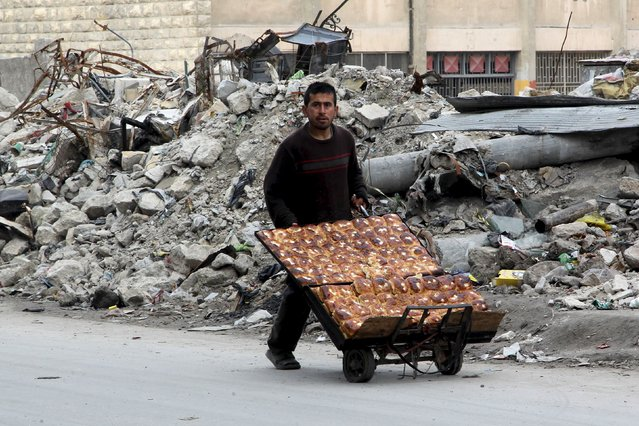 A man selling pastries walks past the rubble of damaged buildings in the rebel held al-Shaar neighborhood of Aleppo, Syria, February 10, 2016. (Photo by Abdalrhman Ismail/Reuters)