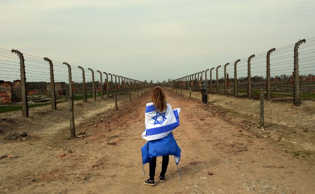A girl with an Israeli flag stands in between a barbed wire fences in at the former Nazi German Auschwitz-Birkenau death camp during the 'March of the Living' at in Oswiecim, Poland on April 16, 2015. The annual march honours Holocaust victims at the former Nazi German Auschwitz-Birkenau death camp in southern Poland. (Photo by Janek Skarzynski/AFP Photo)