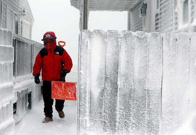 Michael Stanton walks between houses covered in ice from sea spray along the shore in Scituate, Massachusetts, on January 3, 2013. Wind-whipped, fluffy snow continued to fall across the state, buffeted by wind gusts at around 40 miles per hour. The National Weather Service reported Friday morning that the temperature in Boston was 2 degrees, but -20 when the wind chill was factored in. (Photo by Michael Dwyer/Associated Press)