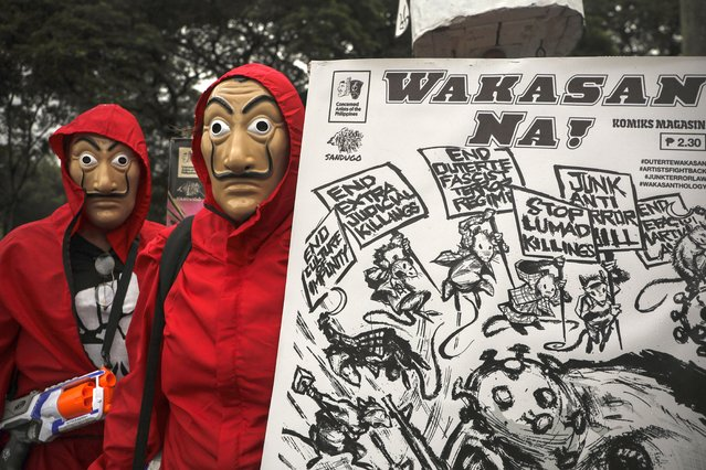 """Protesters wear masks as they hold a slogan that says """"End Now!"""" before marching towards the House of Representatives where Philippine President Rodrigo Duterte is set to deliver his final State of the Nation Address in Quezon city, Philippines on Monday, July 26, 2021. Duterte is winding down his six-year term amid a raging pandemic and a battered economy. (Photo by Gerard Carreon/AP Photo)"""
