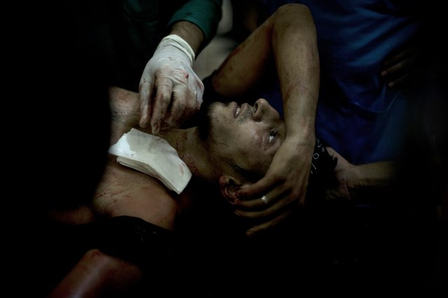A rebel fighter is brought to the Dar al-Shifa hospital in the northern city of Aleppo to be treated for his wounds on October 1, 2012, as fighting in Syria's second largest city between rebel forces and government troops continues. (Photo by Zac Baillie/AFP Photo)