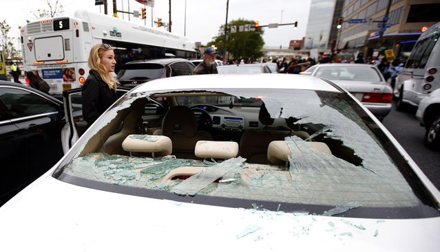 A woman stands by her car with the back window broken out after a march to City Hall for Freddie Gray, Saturday, April 25, 2015 in Baltimore. (Photo by Alex Brandon/AP Photo)