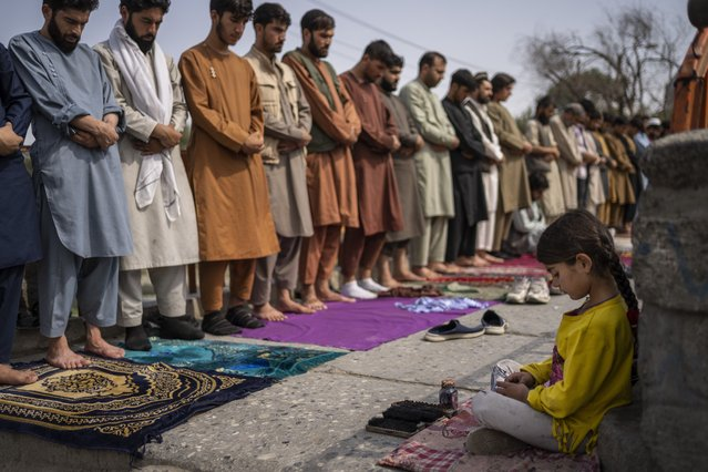 An Afghan girl working as a shoe cleaner sits in the street while men pray during Friday prayers in Kabul, Afghanistan, Friday, September 24, 2021. (Photo by Bernat Armangue/AP Photo)