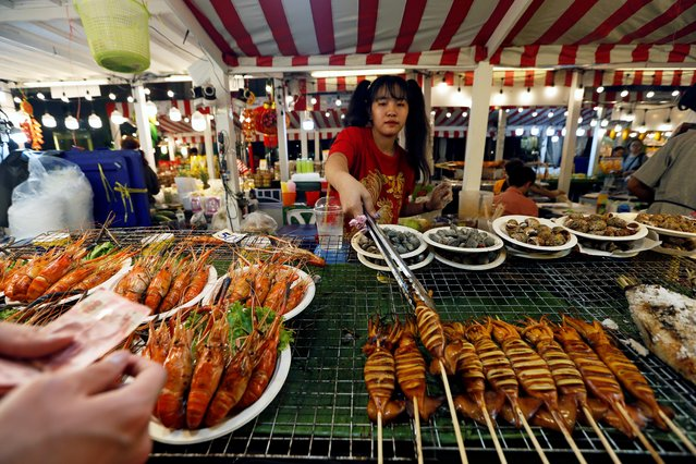 A woman sells seafood in a temporary night market to mark Chinese New Year in Bangkok, Thailand, February 4, 2019. (Photo by Soe Zeya Tun/Reuters)