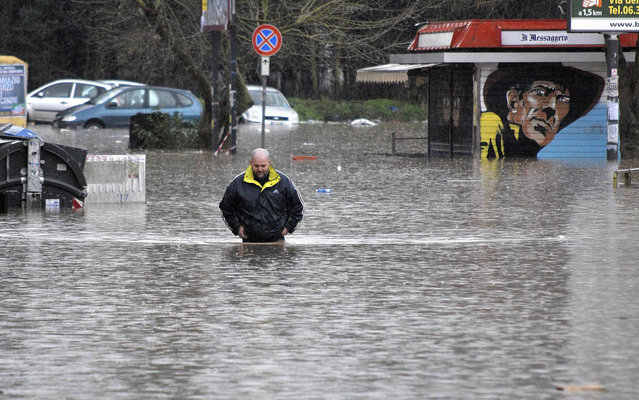 A man walks in a flooded street in Prima Porta neighborhood, in Rome, Italy, Frday January 31, 2014. A torrential rainstorm battered Rome during the night,  causing flash floods that felled trees and blocked thousands of commuters from reaching their workplaces.  (Photo by Daniele Leone/AP Photo/La Presse)