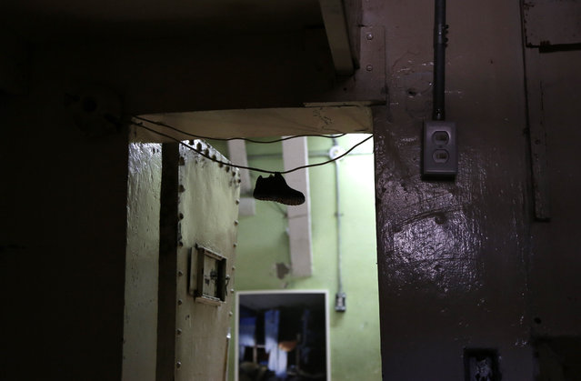 In this April 9, 2015 photo, a child's shoe hangs in the doorway of a cell at the now empty Garcia Moreno Prison, during a guided tour for the public in Quito, Ecuador. Tour guides tell the story of a prisoner who in a jealous rage strangled his wife to death and then hung himself in front of their two children during a family visit years ago. (Photo by Dolores Ochoa/AP Photo)