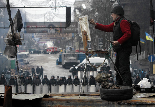 "A man paints on the barricades in front of riot police in central Kiev, Ukraine, Tuesday, February 11, 2014. In a sharp rebuke to Ukrainian President Viktor Yanukovych, the European Union on Monday called for the formation of a new, inclusive government and constitutional reforms that would pave the way to ""free and fair presidential elections"". (Photo by Sergei Chuzavkov/AP Photo)"