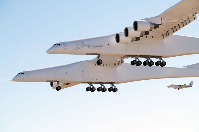 This handout photograph obtained courtesy of Stratolaunch shows the Stratolaunch plane flying over the California desert, April 13, 2019, the first test flight of the US company's gigantic aircraft whose wingspan is almost half that of an Airbus A380. The world's largest airplane – a Stratolaunch behemoth with two fuselages and six Boeing 747 engines – made its first test flight on Saturday, April 13, 2019 in California. The strange aircraft, built by the legendary aeronautical engineering company Scaled Composites in the Mojave Desert, has two fuselages and is powered by six Boeing 747 engines. It must theoretically be used to carry and drop at altitude a small rocket that will then light its engine, and will propel to space to place satellites in orbit. This is a more flexible method of accessing the space than vertical rocket takeoffs, as a large take-off runway would suffice. (Photo by Stratolaunch Systems Corp/AFP Photo/Handout)