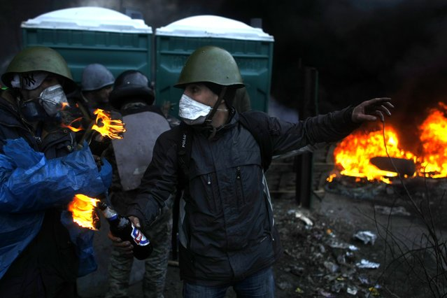 Anti-government protesters get ready to throw petrol bombs on the outskirts of Independence Square in Kiev, Ukraine, Thursday, February 20, 2014. (Photo by Marko Drobnjakovic/AP Photo)