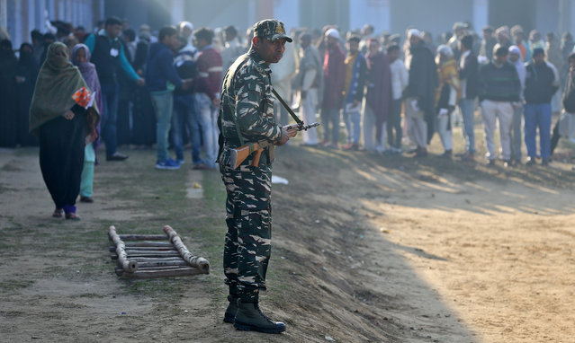 A soldier stands guard as people queue to cast their vote during the state assembly election, in the village of Kairana, in the state of Uttar Pradesh, India, February 11, 2017. (Photo by Cathal McNaughton/Reuters)