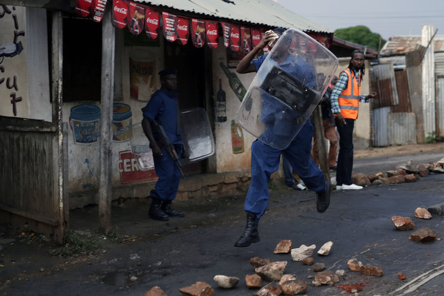A police officer hit by a stone thrown by demonstrators runs as police uses bulldozers and water canons to clear the barricades in the Nyakabyga district of Bujumbura, Burundi, Friday, May 8, 2015. President Pierre Nkurunziza's officially filed to become a candidate for a potential third term in office. (Photo by Jerome Delay/AP Photo)