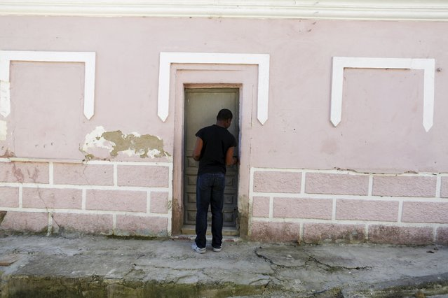 Howard Jackson, a Liberian migrant, closes the door of his home in the Andalusian capital of Seville, southern Spain March 11, 2016. Jackson escaped civil war and spent three years crossing Africa before reaching Spain. Dressed up in one of his more than 200 costumes, from Peter Pan to Little Red Riding Hood, he is a well-known figure at an intersection entering the Spanish city of Seville where he has sold tissues to motorists for over a decade. Jackson is studying law and wants to become a judge. (Photo by Marcelo del Pozo/Reuters)