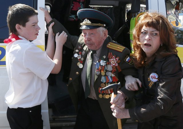 A World War Two veteran (C) is assisted while leaving a van during the celebrations for the Victory Day in the Siberian town of Divnogorsk near Krasnoyarsk, Russia, May 9, 2015. (Photo by Ilya Naymushin/Reuters)
