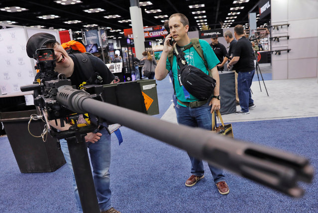 A man looks through the sights of a .50 caliber rifle at the Ohio Ordinance Works during the National Rifle Association (NRA) annual meeting in Indianapolis, Indiana, U.S., April 28, 2019. (Photo by Lucas Jackson/Reuters)