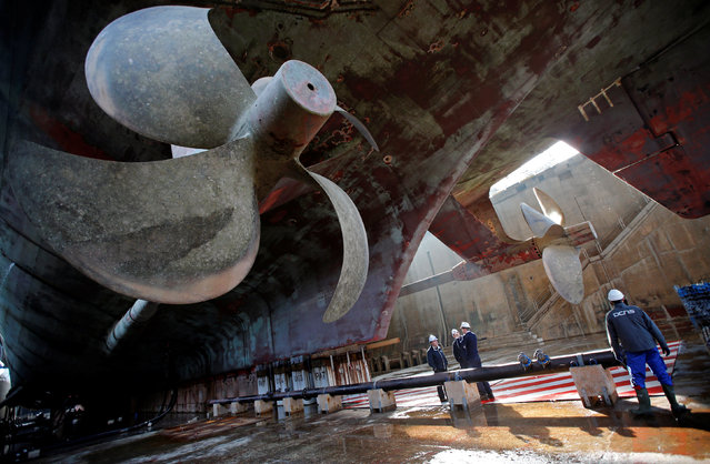 "Technicians work near the propellers on the French nuclear aircraft carrier ""Charles De Gaulle"" that is in dry dock to undergo maintenance and repairs for eighteen months at the Naval base in Toulon, France, February 17, 2017. (Photo by Jean-Paul Pelissier/Reuters)"