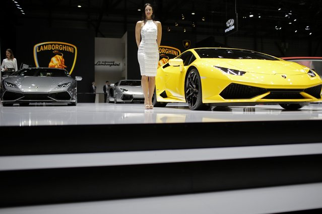 A model poses in front of the new Lamborghini Huracan during the media day of the 84th Geneva International Motor Show, Switzerland, Tuesday, March 4, 2014. The Motor Show will open its gates to the public from March 6 to 16. (Photo by Laurent Cipriani/AP Photo)