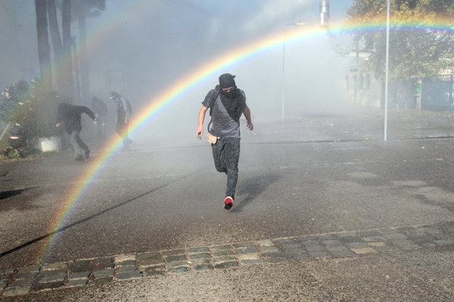 A protester runs from a jet of water shot from a police water cannon in the courtyard of the University of Santiago, during clashes between students and police, in Santiago, Chile, Thursday, May 14, 2015. (Photo by Luis Hidalgo/AP Photo)