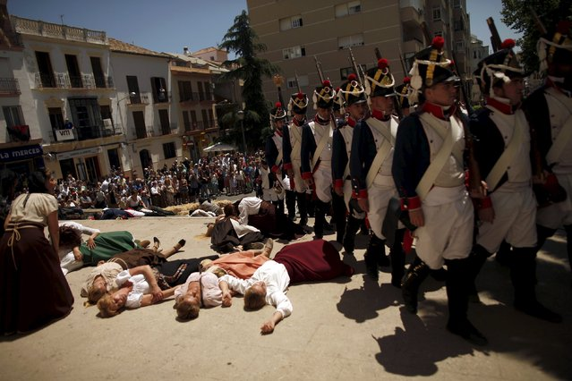 "Members of historical battle re-enactment groups, dressed as bandits and the French army (R), participate in a Spanish Independence War battle re-enactment during the third edition of ""Ronda Romantica"" (Romantic Ronda) in Ronda, southern Spain, May 16, 2015. (Photo by Jon Nazca/Reuters)"