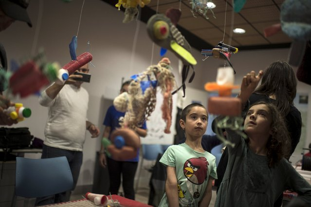 Participants in a workshop organised by Skeleton Sea on how to make sculptures from plastic waste collected from the sea observe a mobile at the Torre Madariaga Biodiversity Centre in Busturia, Spain, May 17, 2015. (Photo by Vincent West/Reuters)