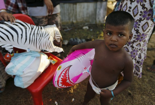 A Rohingya migrant child, who arrived in Indonesia by boat, holds a shark balloon inside a temporary compound for refugees in Kuala Cangkoi village in Lhoksukon, Indonesia's Aceh Province May 17, 2015. (Photo by Reuters/Beawiharta)