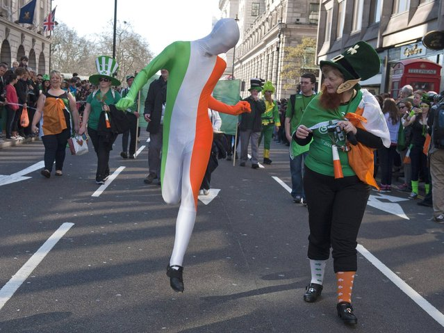 A man wears a full body suit with Irish colors and a woman dressed like a leprechaun attend the St. Patrick's Day parade in central London. (Photo by Will Oliver/EPA)