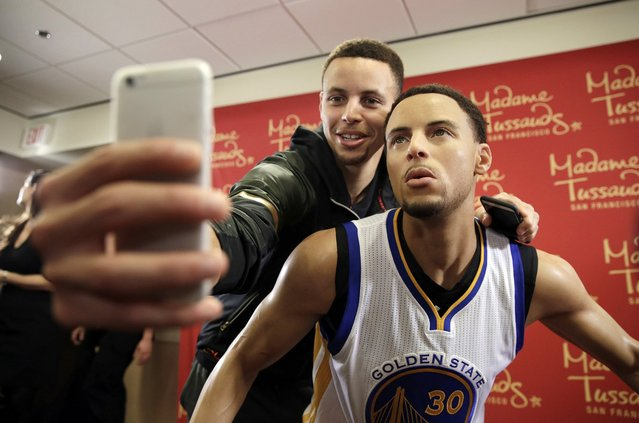 Golden State Warriors guard Stephen Curry, left, takes a selfie with his wax figure by Madame Tussauds after its unveiling Thursday, March 24, 2016, in Oakland, Calif. The figure of the NBA MVP will go on display at Madame Tussauds wax museum at Fisherman's Wharf in San Francisco. (Photo by Eric Risberg/AP Photo)