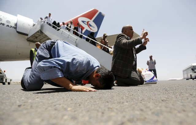 Yemenis, who were stranded in Egypt, pray as they disembark from their plane after returning home, at Sanaa international aiport May 20, 2015. Some 200 Yemenis who have been stuck in Egypt and unable to return home arrived in the capital Sanaa on Wednesday in the first such flight from Egypt, though many more are expected in the coming days and weeks, officials say. (Photo by Khaled Abdullah/Reuters)