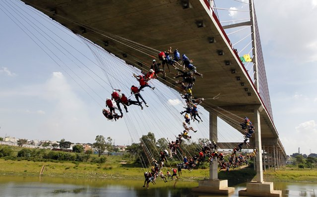 "People jump off a bridge, which has a height of 30 meters (98ft), in Hortolandia, Brazil, April 10, 2016. According to organizers, 149 people were attempting set a new world record for ""rope jumping"", in which people, tied to a safety cord, jump off a bridge. Rope-jumping, an extreme sport, consists in jumping from impressive heights while tied to a nylon rope. Unlike those used in bungee jumping, the rope has no bounce and participants just slow down at the end of the fall. (Photo by Paulo Whitaker/Reuters)"