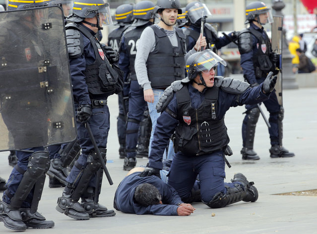 A riot police officer asks for help as a man is injured during a high school protest in Paris, Thursday, April 14, 2016. (Photo by Christophe Ena/AP Photo)