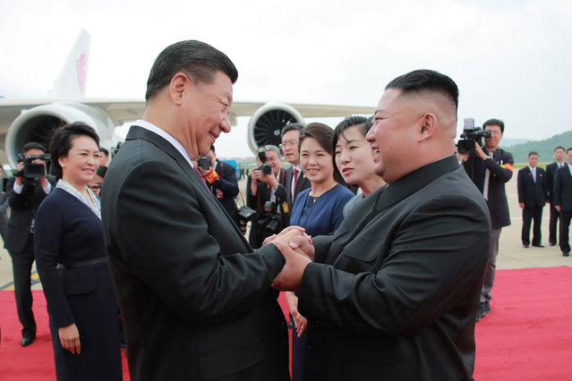 This June 20, 2019 picture released by North Korea's official Korean Central News Agency (KCNA) on June 21, 2019 shows North Korean leader Kim Jong Un (R) shaking hands with Chinese President Xi Jinping upon his arrival at Pyongyang international airport in Pyongyang. North Korean leader Kim Jong Un held talks with Chinese President Xi Jinping in Pyongyang June 20 during a historic visit to burnish an uneasy alliance, as the two men each face challenges of their own with US President Donald Trump. (Photo by KCNA via KNS/AFP Photo)