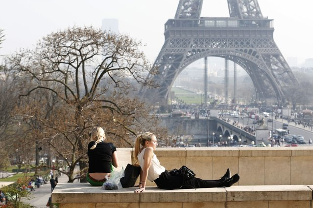 Tourists enjoy the sunny weather in front of the Eiffel tower in Paris, March 14, 2014. (Photo by Charles Platiau/Reuters)