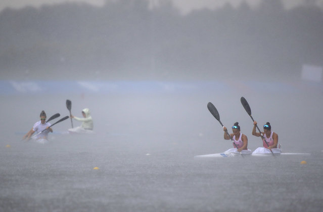 Ana Legacy and Viktoria Schwarz, of Austria, right, Manon Hostens and Sarah Guyot, of France, on left, brave the strong rain as they prepare to compete at the women's K2 canoe sprint 200m final during the Second European Games in Zaslavl, outside Minsk, Belarus, Thursday, June 27, 2019. (Photo by Sergei Grits/AP Photo)