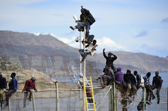 African migrants attempt to scale the fence at the border between Morocco and the North African Spanish enclave of Melilla, on April 3, 2014, in Melilla, Spain. Roughly 70 sub-Saharan migrants tried climb the fence into Melilla this morning, one had to be treated by paramedics. Melilla is a Spanish city and an exclave on the north coast of Africa sharing a border with Morocco. (Photo by Alexander Koerner/Getty Images)