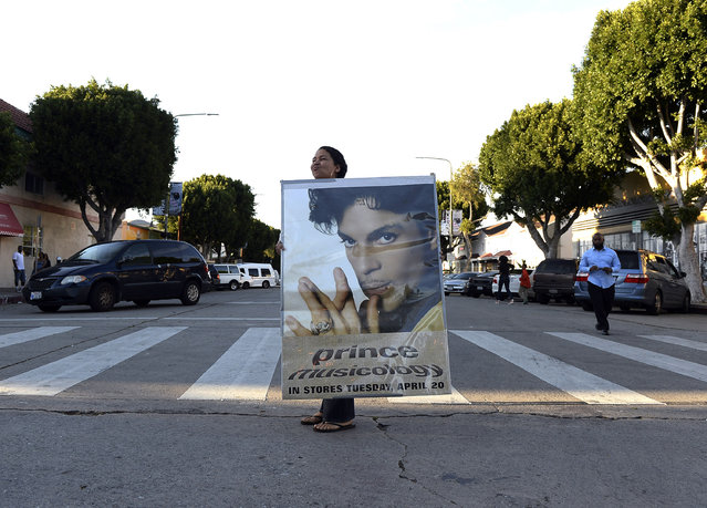 A woman holding a large poster of Prince arrives to a gathering in Leimert Park in memory of musician Prince on April 21, 2016, in Los Angeles, California. (Photo by Kevork Djansezian/Getty Images)
