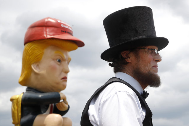 Everett Loud, of Corning, N.Y., and dressed as President Abraham Lincoln, stands near a sculpture of President Donald Trump holding a cell phone while sitting on a toilet before Independence Day celebrations, Thursday, July 4, 2019, on the National Mall in Washington. (Photo by Patrick Semansky/AP Photo)